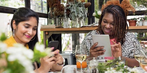 Vrouwen die het concept van de apparatenverbinding bekijken