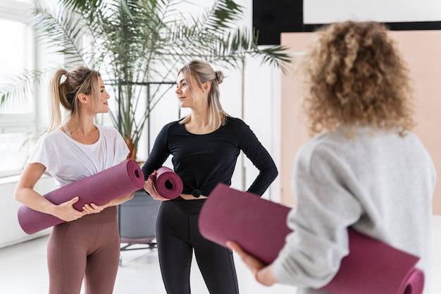 Vrouwen die het middelgroot schot van yogamatten houden