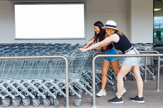 Vrouwen die het winkelen karretje op parkeerplaats voor karren kiezen