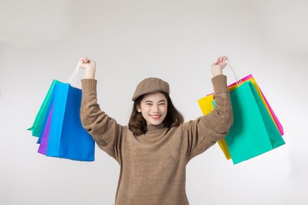 Vrouwen die het winkelen zakken houden die omhoog aan de kant op witte achtergrond bij exemplaarruimte kijken.
