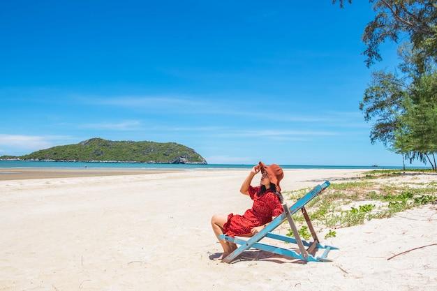 Vrouwen die hoeden dragen, die stoelen op het strand zitten