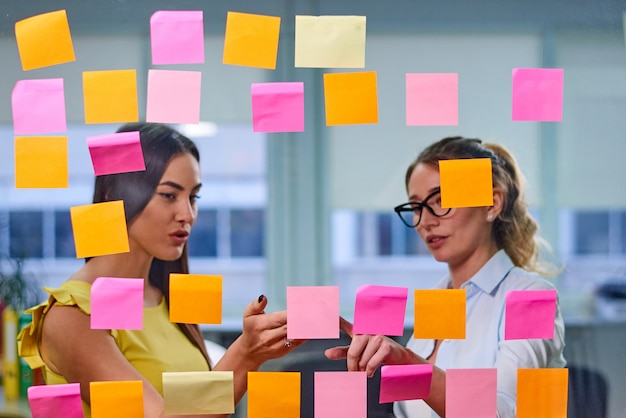 Vrouwen die ideeën op stickers bespreken