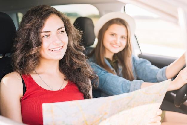 Vrouwen die in auto met kaart zitten