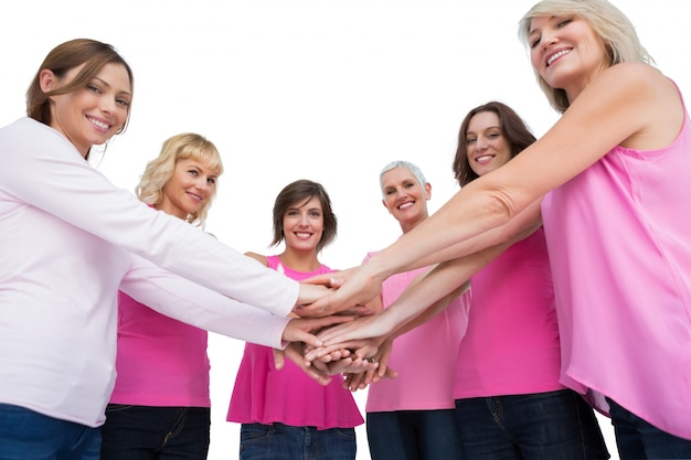 Vrouwen die in de handen van de cirkelholding stellen die camera bekijken die roze voor borstkanker dragen