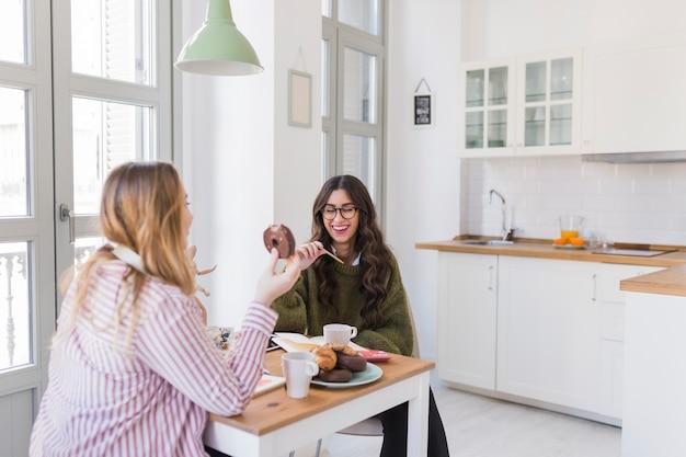 Vrouwen die in de keuken eten en tekenen