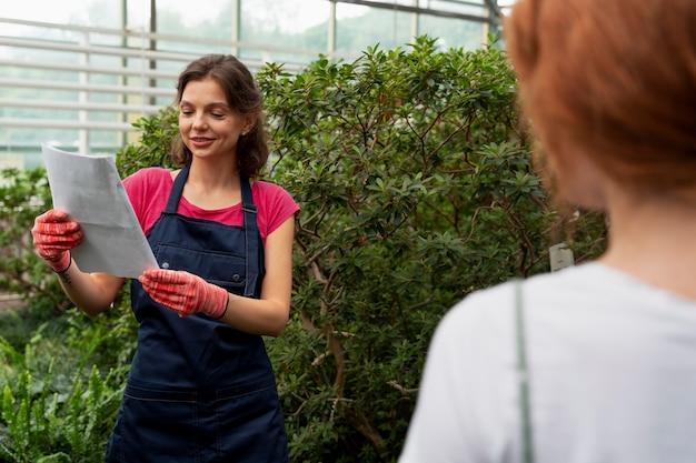 Vrouwen die in een kas voor hun planten zorgen
