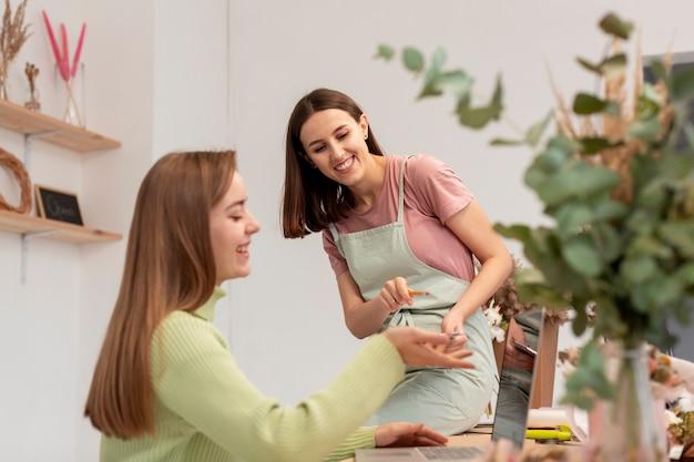 Vrouwen die in haar eigen bloemenwinkel werken