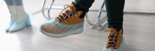 Vrouwen die in lijn zitten met schoenovertrekken op hun voeten close-up