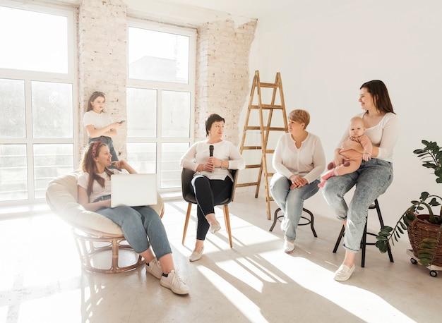 Vrouwen die in witte overhemden het babymeisje bekijken