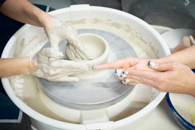 Vrouwen die keramisch aardewerk, concept voor workshop en hoofdklasse maken, vier handenclose-up