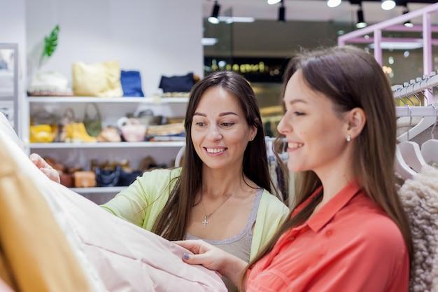 Vrouwen die kleding kopen in de uitverkoop winkelen