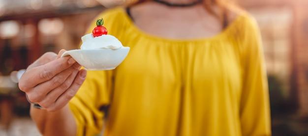 Vrouwen die kleine kom met kaasroom houden