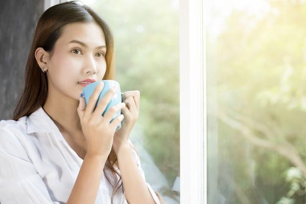 Vrouwen die koffie drinken en wakker worden in haar bed, volledig uitgerust en de gordijnen openen
