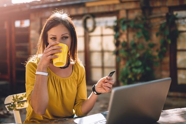 Vrouwen die koffie drinken op het terras in de achtertuin en creditcard gebruiken