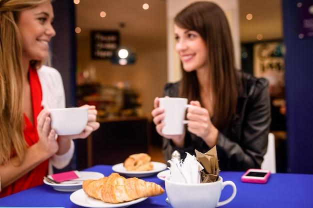 Vrouwen die koffie en snacks hebben bij een koffiewinkel