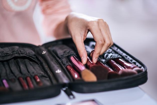 Vrouwen die make-up doen met borstel en schoonheidsmiddel