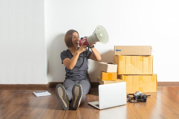 Vrouwen die megafoon met laptop computer van huis houden