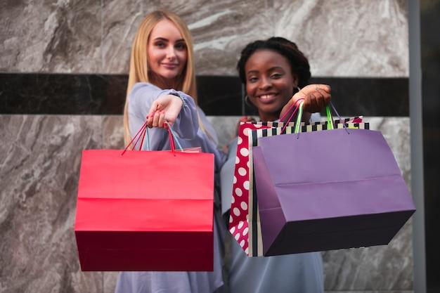 Vrouwen die met het winkelen zakken camera bekijken