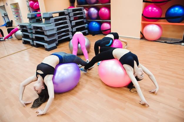 Vrouwen die met oefeningsbal uitwerken in gymnastiek