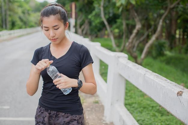 Vrouwen die na het hardlopen water drinken
