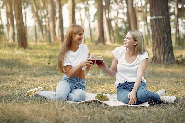 Vrouwen die op een picknick zitten en wijn drinken