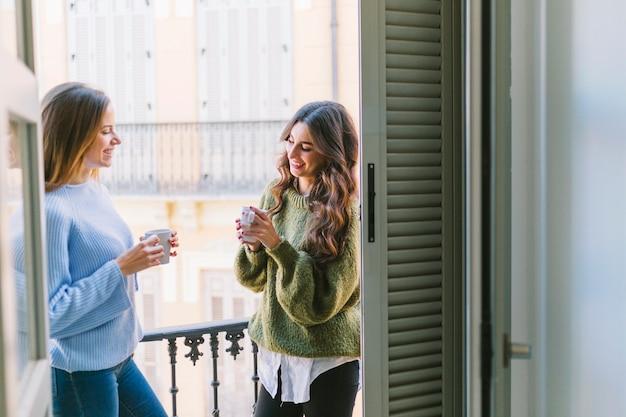 Vrouwen die op het balkon drinken