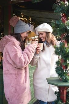Vrouwen die op kerstmarkt glühwein drinken