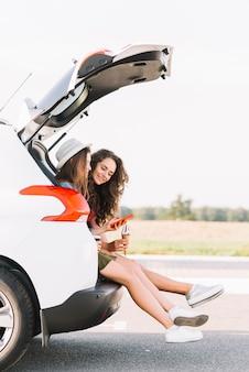 Vrouwen die op kofferbak van witte auto zitten