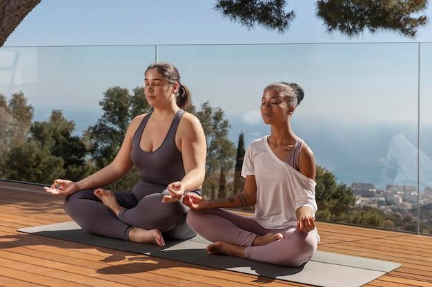 Vrouwen die op yogamat mediteren