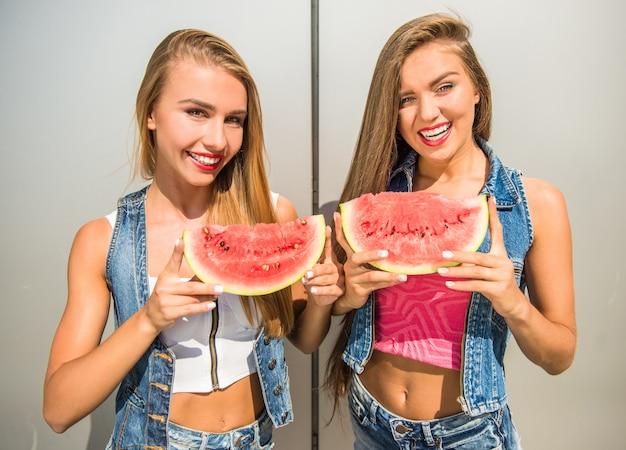 Vrouwen die plakken van watermeloen en het glimlachen houden.
