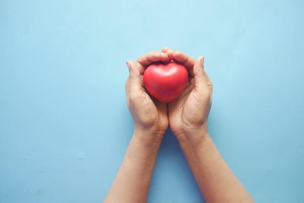 Vrouwen die rood hart op blauwe achtergrond houden