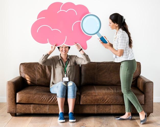 Vrouwen die roze wolkenpictogrammen houden