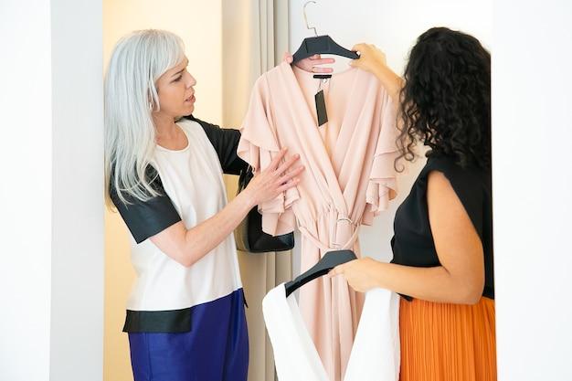Vrouwen die samen in de modewinkel winkelen en jurken met kleerhangers naar de paskamer dragen. consumentisme of winkelconcept