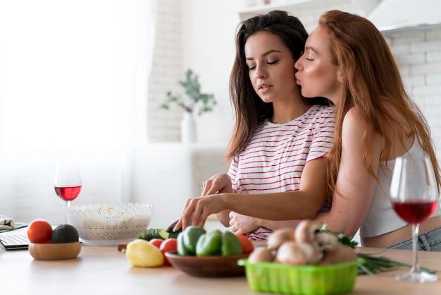Vrouwen die samen thuis een romantisch diner bereiden