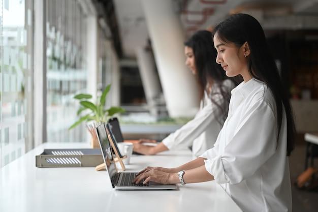 Vrouwen die samenwerken met computerlaptop bij de witte toonbank