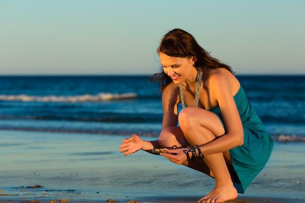 Vrouwen die shells zoeken bij zonsondergang