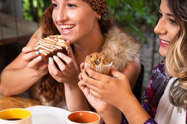 Vrouwen die snoepjes eten bij koffiewinkel