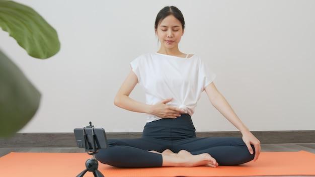 Vrouwen die sportkleding dragen die online cursus yoga op smartphone trainen