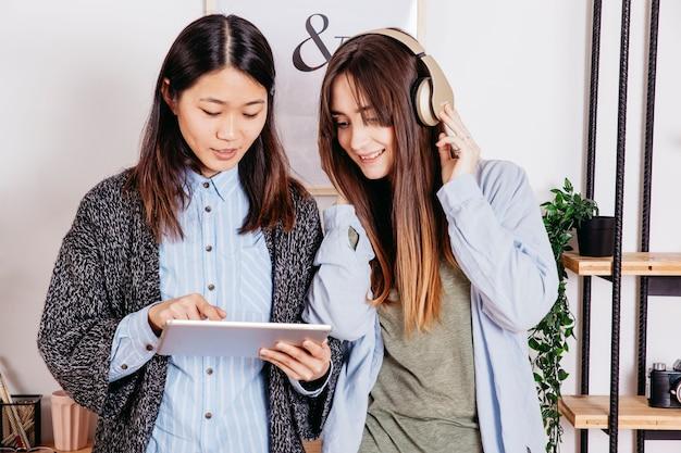 Vrouwen die tablet gebruiken en naar muziek luisteren