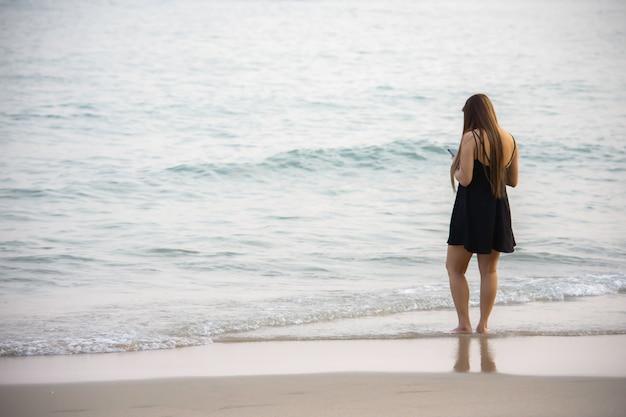 Vrouwen die telefoon ter beschikking op het strand achtergrondoverzees kijken.