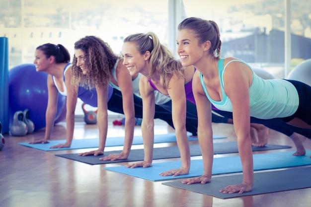 Vrouwen die terwijl het doen van plank glimlachen stellen op oefeningsmat in geschiktheidscentrum