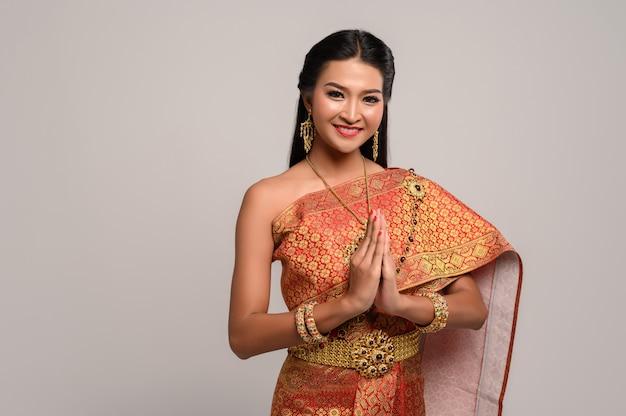 Vrouwen die thaise kleding dragen die respect respecteren, sawasdee-symbool