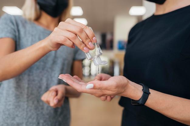 Vrouwen die tijdens een pandemie handdesinfecterend middel gebruiken in de sportschool