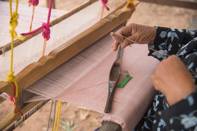 Vrouwen die traditionele thaise fabri in thailand weven.