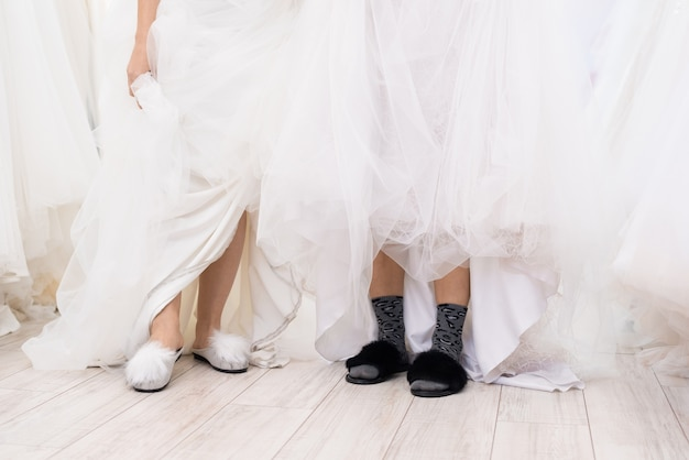 Vrouwen die trouwjurken en pantoffels dragen