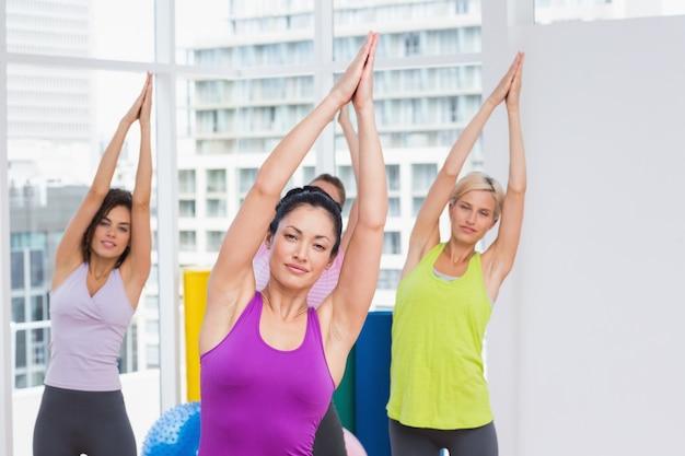 Vrouwen die uitrekkende oefening in gymnastiek uitoefenen
