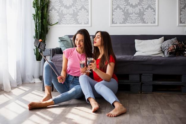 Vrouwen die wijn drinken en foto's maken