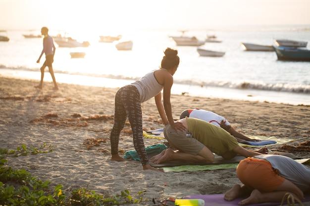 Vrouwen die yoga-oefeningen doen of ondersteunde duiven poseren op het lege strand van de indische oceaan in mauritius