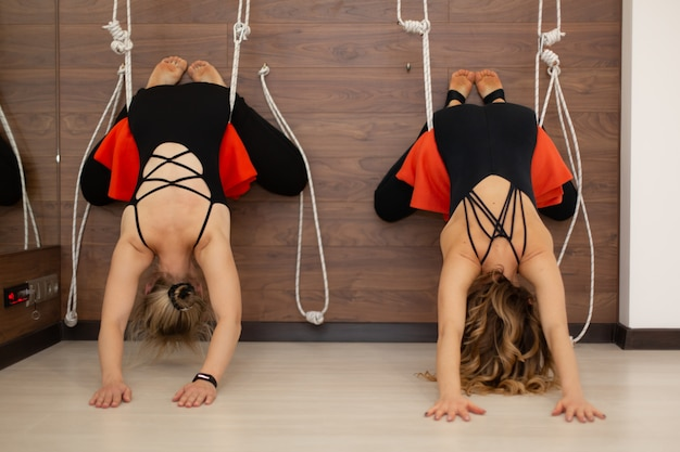 Vrouwen die yoga op kabels uitoefenen die zich in gymnastiek uitrekken. fit en wellness levensstijl