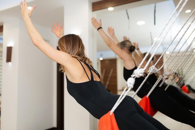 Vrouwen die yoga op touwen uitoefenen die zich in gymnastiek uitrekken. fit en wellness levensstijl